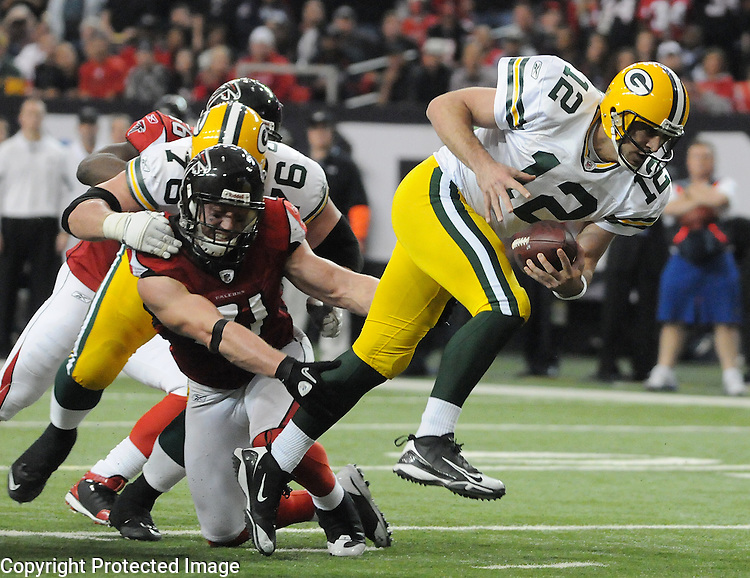 Green Bay Packers quarterback Aaron Rodgers slips past Atlanta Falcons' Kroy Biermann for a touchdown during the third quarter of the game at the Georgia Dome in Atlanta, Ga., on Nov. 28, 2010.