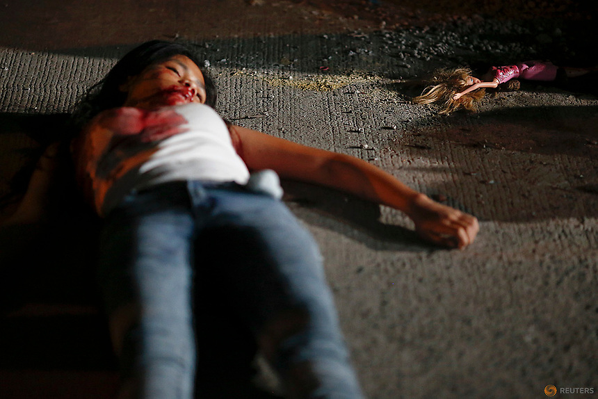 "A 17 year old girl lays dead next to her doll after she and her friend were killed by unknown motorcycle riding gunmen in an alley in Manila, Philippines early October 26, 2016. According to the police, a sign on a cardboard reading ""Tulak ka, hayop ka"", which translates to ""You are a (drug) pusher, you are an animal"" was found with the the body of girl's killed friend.   REUTERS/Damir Sagolj"