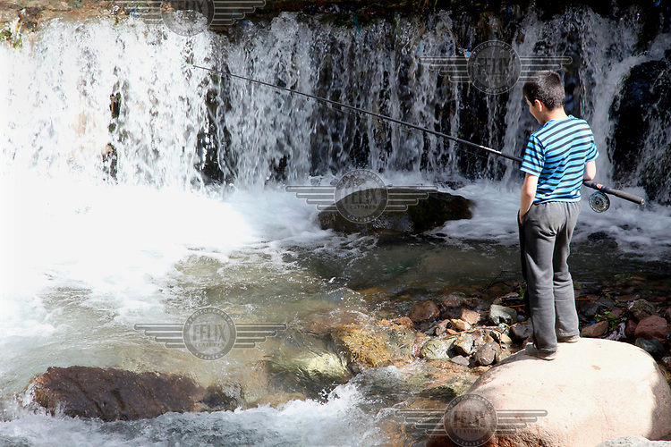 A boy fishing in a river in the village of Zimchurud.