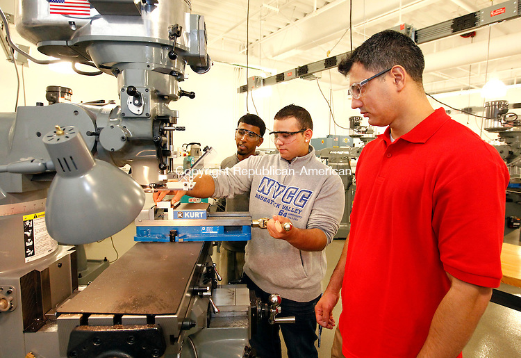 Waterbury, CT-03 October 2012-100312CM01-  Naugatuck Valley Community College student, Jariam Oliveras, center, demonstrates the operation of a Bridgeport Vertical Miller inside the Advanced Manufacturing Technology Center at NVCC Wednesday afternoon in Waterbury.  With Oliveras are fellow students, Edgar Ortiz, right, and Davendra Algoo.  The trio were among the students that were on hand for the official grand opening of the school's new center.   Christopher Massa Republican-American