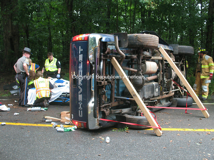 WOODBURY, CT - 23 July 2010 - 072310RH01 - Emergency workers treat a drive who flipped his pickup on Middle Road Turnpike in Woodbury