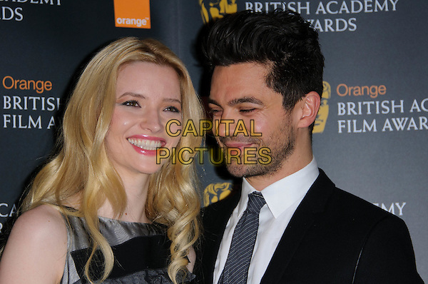 TALULAH RILEY & DOMINIC COOPER.The nominations for The Orange British Academy Film Awards (BAFTAs) at BAFTA headquarters, London, England..January 18th, 2011.headshot portrait black grey gray tie trophy award sleeveless stubble facial hair smiling.CAP/CJ.©Chris Joseph/Capital Pictures.