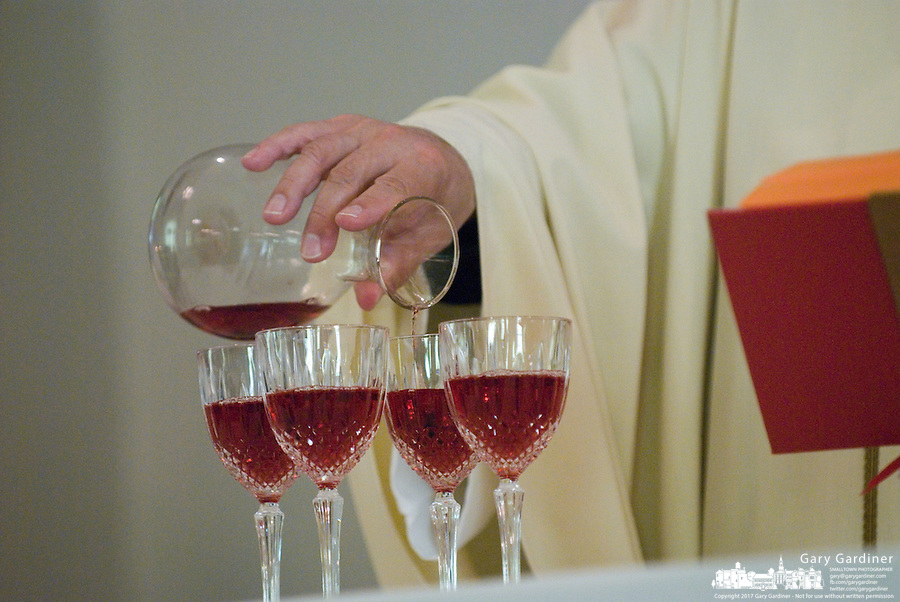 A priest pours wine for a  first communion sacrament at a Catholic church in Johnstown, OH.<br />