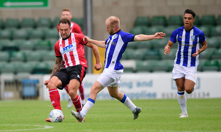 Lincoln City's Neal Eardley vies for possession with Sheffield Wednesday's Barry Bannan<br /> <br /> Photographer Chris Vaughan/CameraSport<br /> <br /> Football Pre-Season Friendly - Lincoln City v Sheffield Wednesday - Saturday July 13th 2019 - Sincil Bank - Lincoln<br /> <br /> World Copyright © 2019 CameraSport. All rights reserved. 43 Linden Ave. Countesthorpe. Leicester. England. LE8 5PG - Tel: +44 (0) 116 277 4147 - admin@camerasport.com - www.camerasport.com