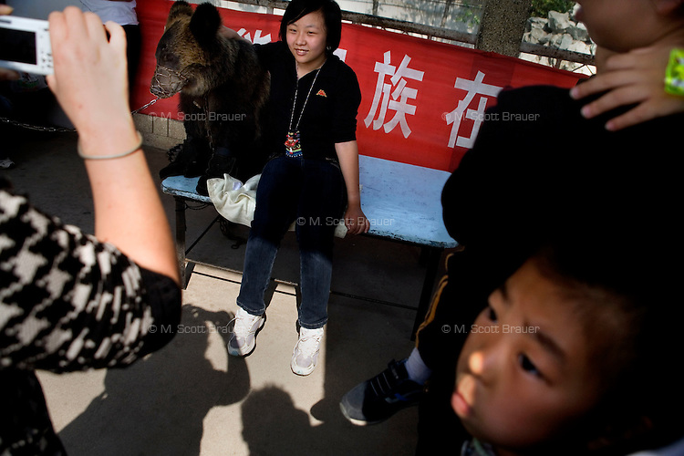 A visitor to the zoo poses with a bear wearing a muzzle in the Tianjin Zoo in Tianjin, China.