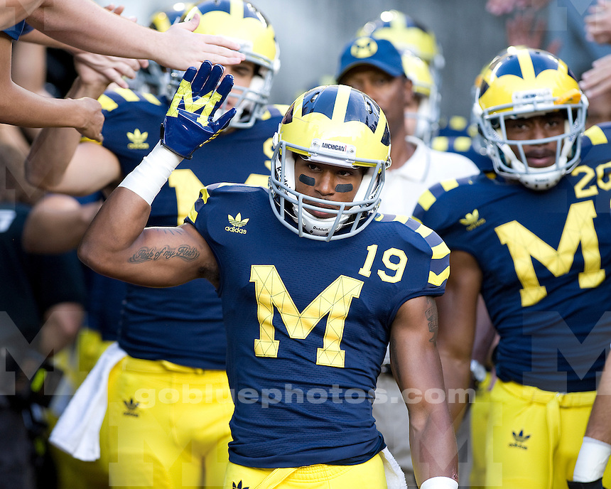 Saturday, September 10th. Michigan's Kelvin Grady and his teammates sport throwback uniforms as they exit the tunnel for the first ever night game at Michigan Stadium. Michigan defeats Notre Dame, 35-31, in first ever night game at Michigan Stadium, Satruday night, September 10th, 2011.