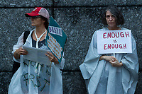 "Organisers:, Sarajean Rossitto (left) and Jenise Treuting (right) join other  American and Japanese  people at the  ""Enough is Enough"" rally in Toranomon, Tokyo Japan, Tuesday August 15th 2017. Around 20 people gathered to take part in a global day of action demanding fairer policies in the United States that do not favour only the rich and do not remove human rights from ordinary people. A silent vigil was held for 30 minutes at 6pm so that the voices that could be heard after spoke louder. This is the closest it is possible to protest to the US embassy in Tokyo."