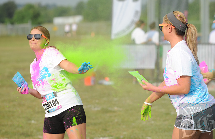 NWA Media/ANDY SHUPE - Cassie Gierach of Bentonvile, left, laughs as her friend Rachael Sheridan of Rogers throws color at her before the start of the Color Vibe 5K held in partnership with 7hills Homeless Center Saturday, July 19, 2014, at the Washington County Fairgrounds in Fayetteville. Participants ran through various stations where volunteers threw colored cornstarch at them. Visit photos.nwaonline.com for more photographs from the event.