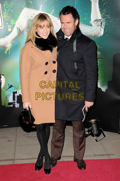 "GABBY LOGAN & KENNY LOGAN.VIP Gala Premiere of Cirque de Soleil -  ""Quidam"" at the Royal Albert Hall, London, England. .January 6th 2009.full length brown camel tan coat husband wife couple black grey gray fur gaby bag purse .CAP/CAS.©Bob Cass/Capital Pictures."