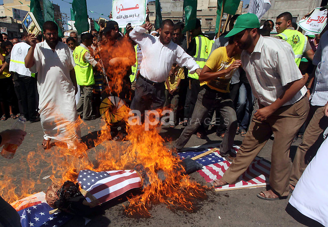 Palestinians burn the Israeli and the U.S. flags during a demonstration against the controversial film 'Innocence of Muslims' in Khan Younis southern Gaza strip, on September 14, 2012. The controversial low budget film reportedly made by an Israeli-American which portrays Muslims as immoral and gratuitous, sparked fury in Libya, where four Americans including the ambassador were killed on Tuesday when a mob attacked the US consulate in Benghazi, and has led to protests outside US missions in Morocco, Sudan, Egypt, Tunisia and Yemen. Photo by Ashraf Amra