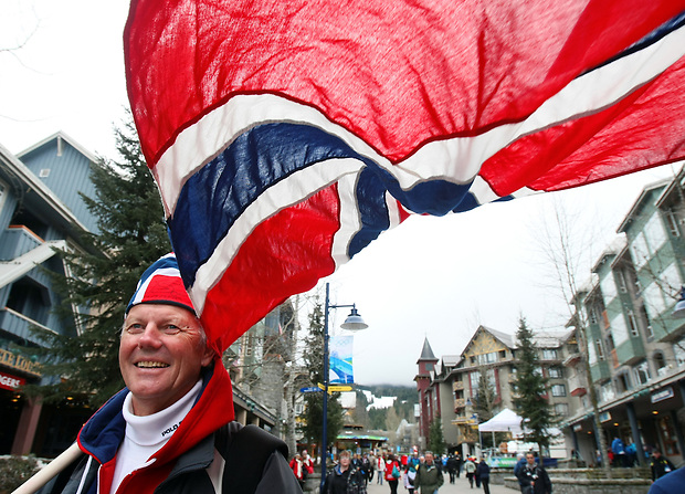 Stein Rohdehanssen of Oslo, Norway flies the Norwegian flag and a large smile in Whistler Village after cheering Norway to the gold medal in the ladies' 4x5 km cross country relay during the XXI Olympic Winter Games in Whistler, British Columbia.