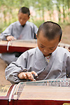 Young students of a Shaolin martial arts school learning to play guzheng, Chinese zither in DengFeng, Henan, China 2014