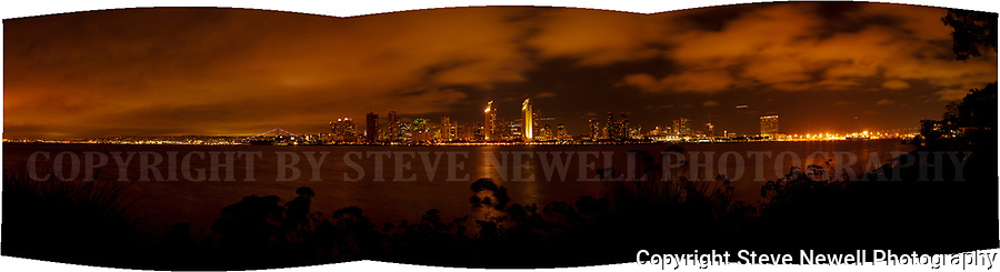 Downtown San Diego cityscape with clouds overhead that are being illuminated by the nighttime city lights creating an orange hue to the low flying cloud cover!