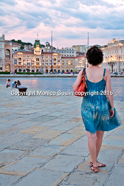 Standing on the Molo Audace pier, looking towards Piazza Unita d'Italia at sunset in Trieste, Italy