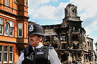 A policeman stands near a burnt out building destroyed during a riot in Tottenham. London saw the beginnings of riots on Saturday evening, after a peaceful protest in response to the shooting by police of Mark Duggan during an attempted arrest, escalated into violence. By the third night of violence, rioting and looting had spread to many areas of the capital and to other cities around the country.