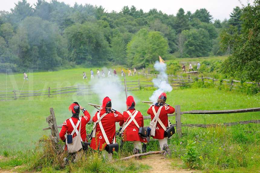 The King's Own Regulars, the Light Infantry Company of His Majesty's Fourth Regiment of Foot, fire on Colonial militiamen at a Revolutionary War encampment, Old Sturbridge Village, Massachusetts, USA.
