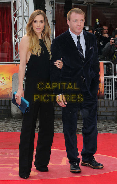 Jacqui Ainsley & Guy Ritchie.'African Cats' UK Premiere at BFI Southbank, London, England..25th April 2012.full length married husband wife black suit blue trousers top blue clutch bag.CAP/CAN.©Can Nguyen/Capital Pictures.