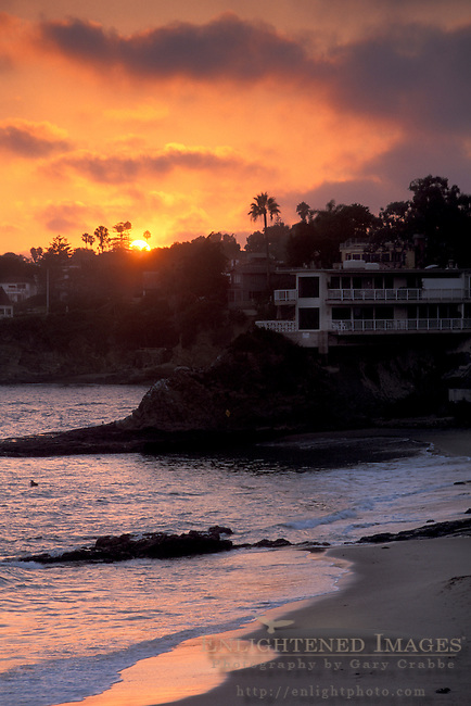 Golden orange sunset over palm trees, apartment, and sandy ocean beach shore, on the coast at Laguna Beach, California