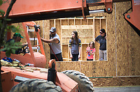 NWA Democrat-Gazette/CHARLIE KAIJO (From left) David Kronberg of Branson Mo. helps direct a machine while daughters Hannah, 12, and Alyssa, 6, and wife Rhiannon watch, Friday, June 8, 2018 on Passion Play Road, across the street from the Washington Regional clinic in Eureka Springs. <br /><br />Eight tiny houses are being built in Eureka Springs, which has a dearth of affordable housing. They're being constructed by 66 volunteers from 13 states with World Mission Builders. They began work on Monday (June 4) and should finish most of the construction by the end of next week (June 15). Then local volunteers will finish out the interiors and put shingles on the roofs. The first eight houses are part of what will be called ECHO Village. Plans are to eventually have 26 houses in the village. It's a project of Eureka Christian Health Outreach, which bought 10 acres for the village. The same group started ECHO Clinic in Eureka Springs in 2005. It provides free medical care to the uninsured and people on a low income.