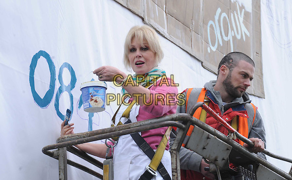 JOANNA LUMLEY.attends a photocall to paint a Vauxhall billboard as part of the Thames Reach Fundraising campaign, London, England, UK, March 29th 2010..half length pink top white dungarees overalls painting paint pot charity work scarf  brush poster .CAP/DS.©Dudley Smith/Capital Pictures