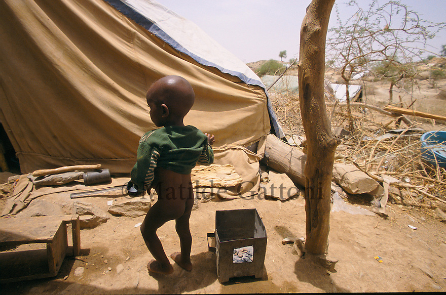 Eritrea - Debub- Baby walking in the IDP camp. As a result of 30 years of war for independence against Ethiopia (from 1961 to 1991) and another 3 years from 1997 to 2000, there are 50,000 Eritreans currently living in internally displaced (IDP) camps throughout the country. These IDPs have fled three times in the last 10 years, each time because of renewed military conflict. They lived in relatives' homes when lucky enough, but mostly, the fled to the mountains, where they attempted to do what Eritreans do best, survive. Currently there is no Ethiopian occupation in Eritrea, but landmines prevent the IDPs from finally going home. .It is estimated that every Eritrean family lost two or three members to the war which makes the reality of the current emergency situation even more painful for Eritreans worldwide. Currently, the male population has been decreased dramatically, affecting the most fundamental socio-economic systems in the country. Among the refugee population, an overwhelming majority of families are female-headed, severely affecting agricultural production. For, IDPs in particular, 80% of households are female-headed..The unresolved border dispute with Ethiopia remains the most important drawback to Eritrea's socio-economic development, as national resources (human and material) continue to be prioritized for national defense. Eritrea is vulnerable to recurrent droughts and variable weather conditions with potentially negative effects on the 80 percent of the population that depend on agriculture and pastoralism as main sources of livelihood. The situation has been exacerbated by the unresolved border dispute, resulting in economic stagnation, lack of food security and increased susceptibility of the population to various ailments including communicable diseases and malnutrition..