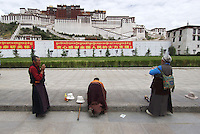 Pilgrims pray and prostrate outside the Potala Palace in Lhasa, Tibet..13 Jul 2006