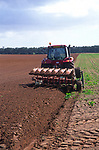 A0742H Red tractor ploughing a field in Suffolk Sandlings England