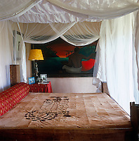 A large painting redolent of Gauguin's Tahitian scenes and painted by Gabriela Trzebinski can be seen through the mosquito netting in the bedroom