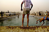 "Abu Graibh, near Baghdad, October 20, 2002.Young Iraqis swimming in an irrigation canal at dusk, national pride rides high as can be seen by this teenager t-shirt that reads""Iraq"" on the back."