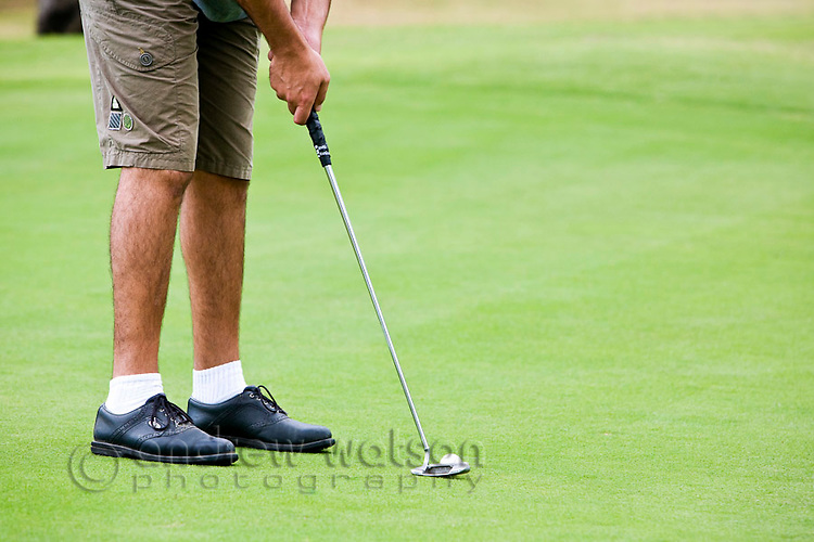 Golfer putting ball on green.  Paradise Palms Golf Course, Kewarra Beach, Cairns, Queensland, Australia