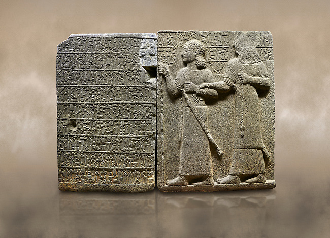 "Photo of Hittite monumental relief sculpted orthostat stone panel of Royal Buttress. Basalt, Karkamıs, (Kargamıs), Carchemish (Karkemish), 900-700 B.C. Anatolian Civilisations Museum, Ankara, Turkey.<br /> <br /> Hieroglyph panel (left) - Discourse of Yariris. Yariris presents his predecessor, the eldest son Kamanis, to his people. <br /> Right Panel - King Araras holds his son Kamanis from the wrist. King carries a sceptre in his hand and a sword at his waist while the prince leans on a stick and carries a sword on his shoulder. <br /> <br /> Hieroglyphs reads; ""This is Kamanis and his siblings.) held his hand and despite the fact that he is a child, I located him on the temple. This is Yariris' image"".  <br /> <br /> Against a brown art background."