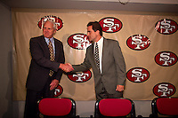 SANTA CLARA, CA - New head coach Steve Mariucci of the San Francisco 49ers is introduced to the media and shakes hands with Bill Walsh at the 49ers facility in Santa Clara, California in 1997. Photo by Brad Mangin