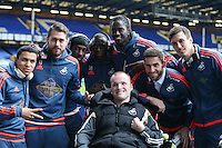 Swansea City players pose pitch side with a disabled supporter ahead of the Barclays Premier League match between Everton and Swansea City played at Goodison Park, Liverpool