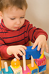 Two year old toddler boy playing with peg and block toy turning block to fit on spindle