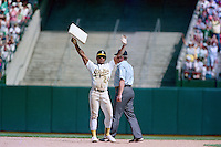 OAKLAND, CA - Rickey Henderson of the Oakland Athletics holds up second base after stealing it during a game at the Oakland Coliseum in Oakland, California in 1991. Photo by Brad Mangin