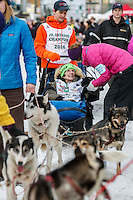 Honorary musher, Joanne Potts in the sled of Jr. Iditarod champion Kevin Harper just prior to leaving the Ceremonial Start of the 2016 Iditarod in Anchorage, Alaska.  March 05, 2016