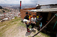 SOACHA, COLOMBIA - APRIL 15: A family carry a bag after the local government workers delivered food to the community during the mandatory preventive quarantine to prevent the spread of the new coronavirus in Soacha Colombia on April 15, 2020. Soacha's mayor visited the slums of the town handing out baskets of food to help families in difficult financial times due to Covid-19 pandemic. (Photo by Leonardo Munoz/VIEWpress via Getty Images)