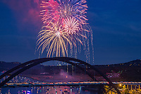 Independence Day fireworks display towers over the 360 Bridge as boaters view on the waters of Lake Austin.