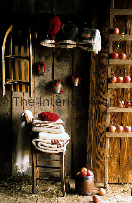 A sled and cow bells hang from the wall pf this simple barn above a chair piled wth blankets and next to a ladder decorated with red apples
