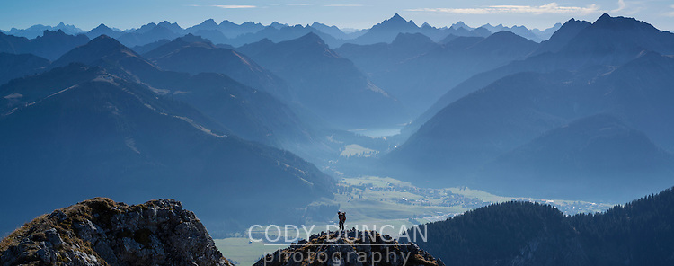 Climber on summit of Aggenstein (1987m) with Tannheimer Tal (Aus.) in background, Allgäu, Bavaria, Germany