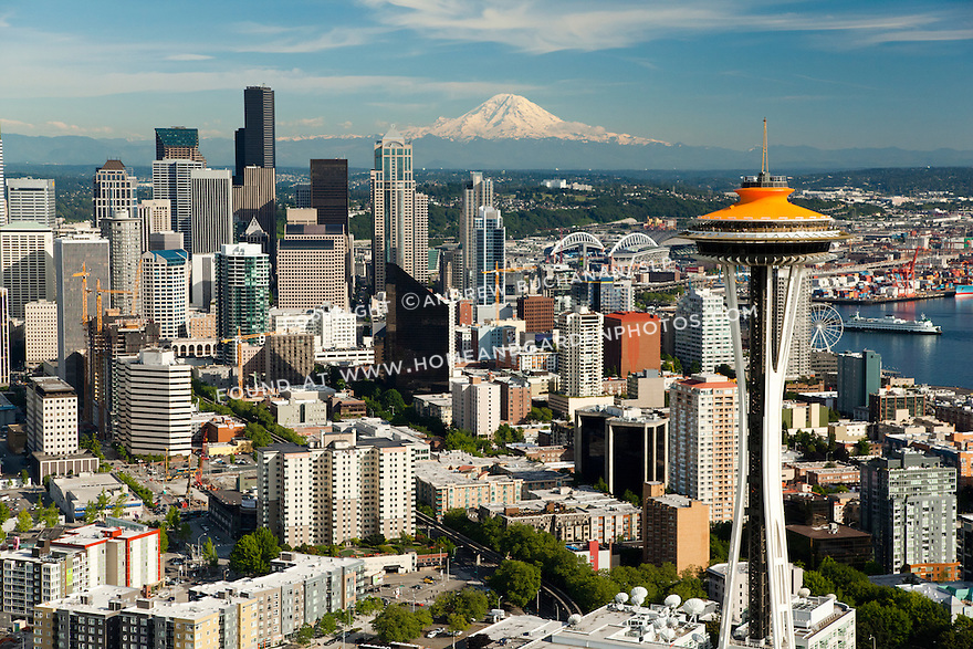 top of Space Needle painted orange for its 50th Anniversary celebration with skyscrapers of downtown Seattle skyline and Mount Rainier behind; Seattle, WA