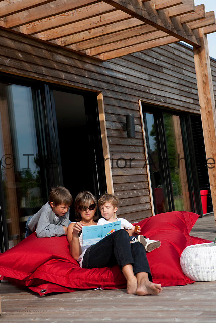 Architect Delphine Bouchet and her two boys relax on a massive red cushion on the terrace