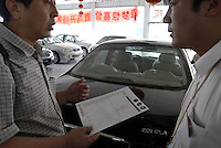 "A salesman talks with a customer who is interested in a Nissan ""Bluebird"" in a Dongfeng Nissan dealership, Beijing, China.."
