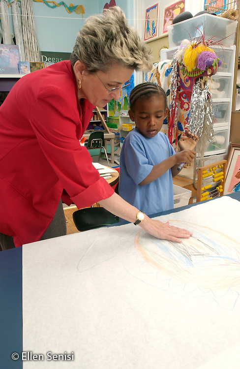 MR / Schenectady, NY.Yates Arts-in-Education Magnet School.Full-Day Pre-K class; urban school.State Funded through NYS Universal Pre-K Program.Teacher talks to boy (4, African-American) about his drawing..MR: Fel3, Bea2.©Ellen B. Senisi