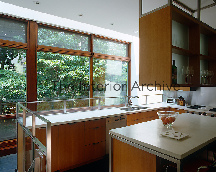 This compact contemporary kitchen has views through floor to ceiling windows to the garden beyond