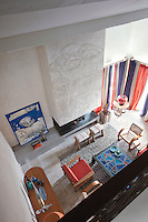 A view from the mezzanine to the living area below, with a chequered Moroccan rug covering the travertine floor