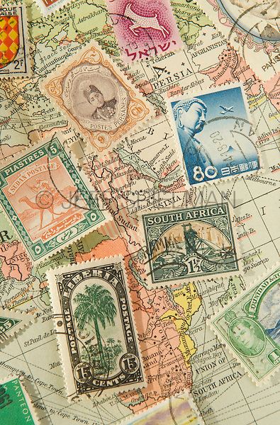 Assortment of Colorful Vintage Postage Stamps from Various Countries Around the World against a 1929 Map of the World<br /> <br /> AVAILABLE FOR COMMERCIAL OR EDITORIAL LICENSING FROM PLAINPICTURE.COM.  Please go to www.plainpicture.com and search for image # p569m791801.