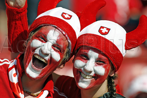 13 June 2006: Two Swiss fans with their faces painted in the crowd before the Fifa World Cup Group G match between France and Switzerland played in Stuttgart, Germany. The game ended in a 0-0 draw. Photo: Neil Tingle/actionplus....060613 soccer football man male men woman women female support supporter fan face paint