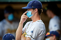 Savannah Bananas Ben Anderson (20) wears a mask, while standing outside the dugout to practice social distancing, during a Collegiate Summer League game against the Macon Bacon on July 15, 2020 at Grayson Stadium in Savannah, Georgia.  (Mike Janes/Four Seam Images)