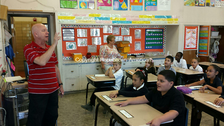WATERBURY -- Chase Elementary School music teaher Chris Ouellette leads fourth graders rehearsing a song about Astronaut Rick Mastracchio.